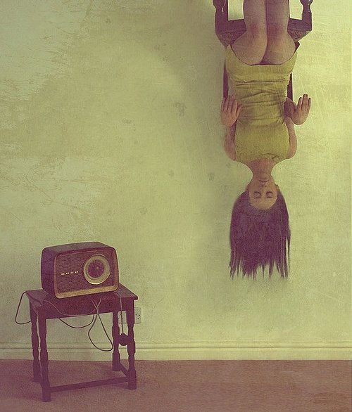 Photo of woman sitting upside down with old radio