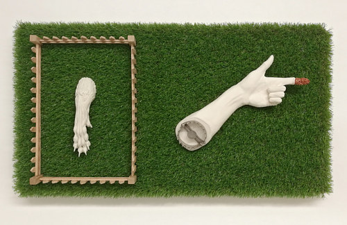 A wall-hanging sculptural piece with imitation grass