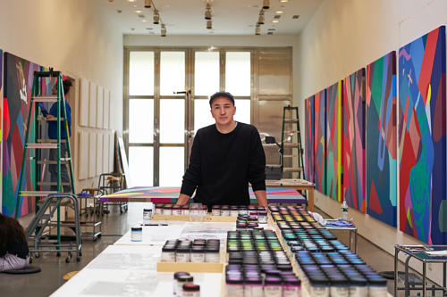A photo of artist KAWS in his studio
