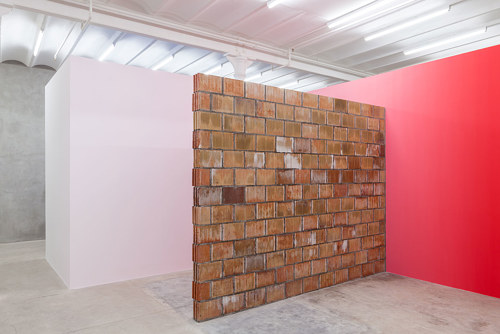 An installation with a red gradient painted on a wall next to brickwork