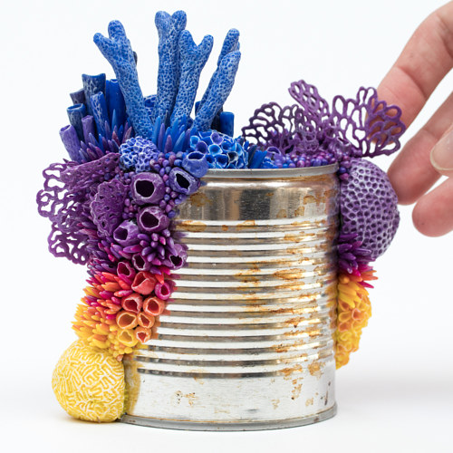 A tin can with colourful coral sculptures on it