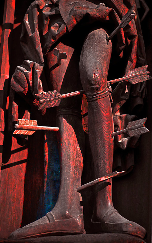A photo of a wooden sculpture of a figure shot through with arrows