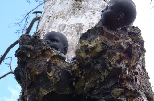 A sculpture consisting of doll heads affixed to a tree