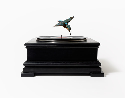 A sculptural artwork with a bird serving as the needle on a record player