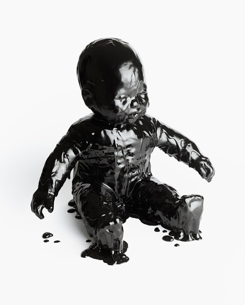 A baby doll coated in black tar-like resin