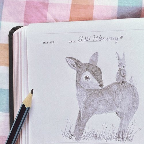 sketchbook with drawing of a deer and a pencil