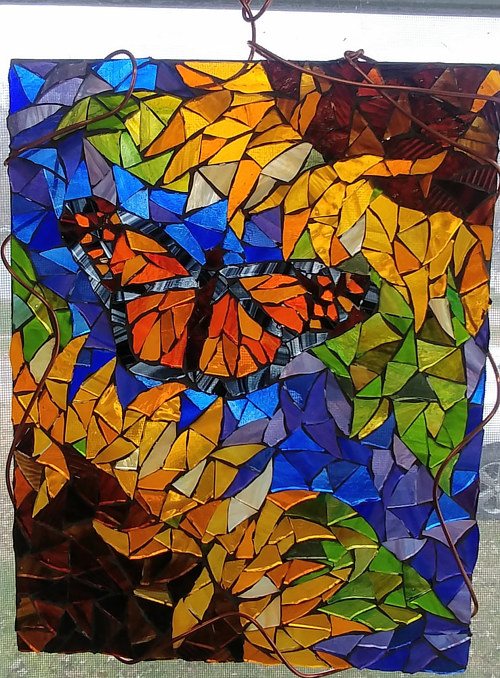 A hanging stained glass artwork depicting a butterfly and flowers