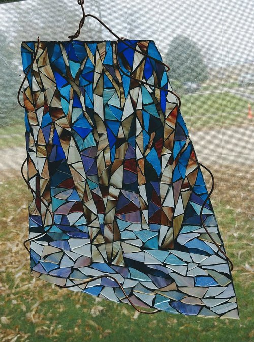 A stained glass artwork with an image of birch trees