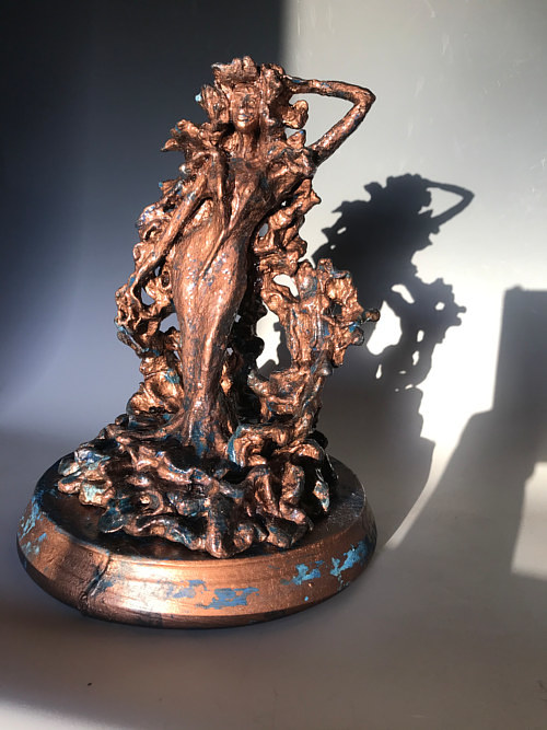 A sculoture of a female figure with a bronzed finish