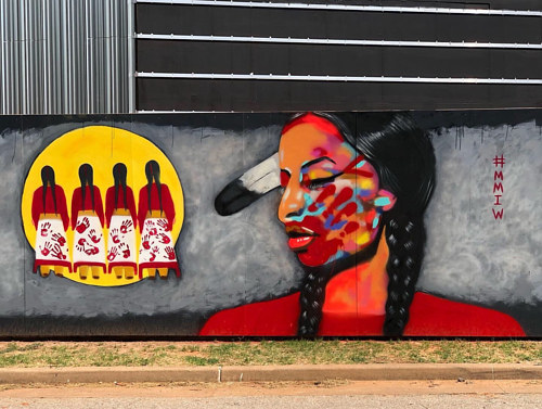 A mural featuring a woman in profile painted in bright colour