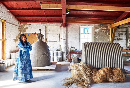 A photo of artist Simone Leigh in a sculpture studio