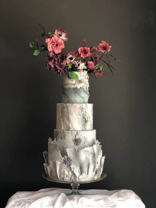 An artisan cake topped with realistic sugar flowers