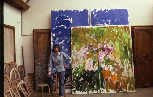 A photo of Joan Mitchell standing in her painting studio