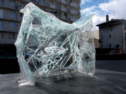 An outdoor installation of fragmented glass around a bus stop