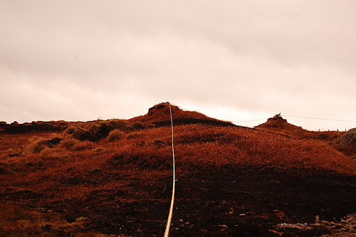 A photo of a rope pulled across a red landscape