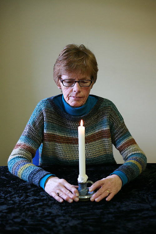 A photo of a woman staring intently at a candle