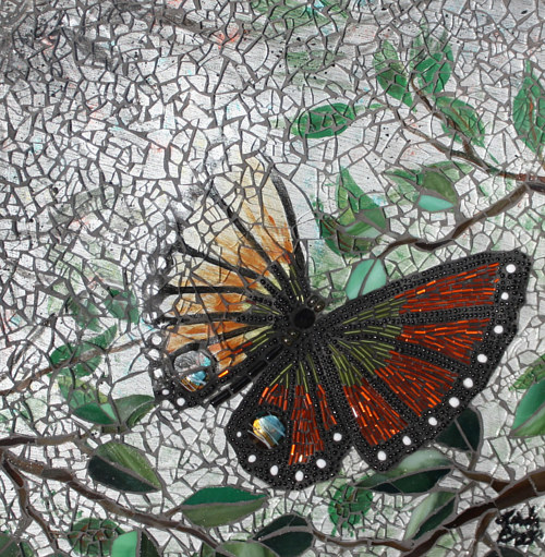 A mosaic artwork depicting a butterfly flying through mist
