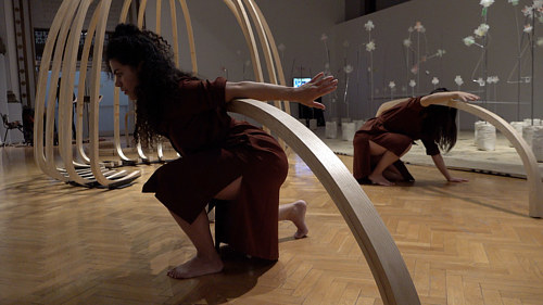 A photo of a dance performance held in a space with sculptural objects