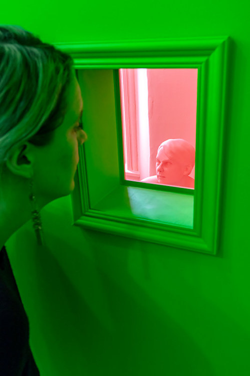 A view of an art installation with green walls and realistic figures