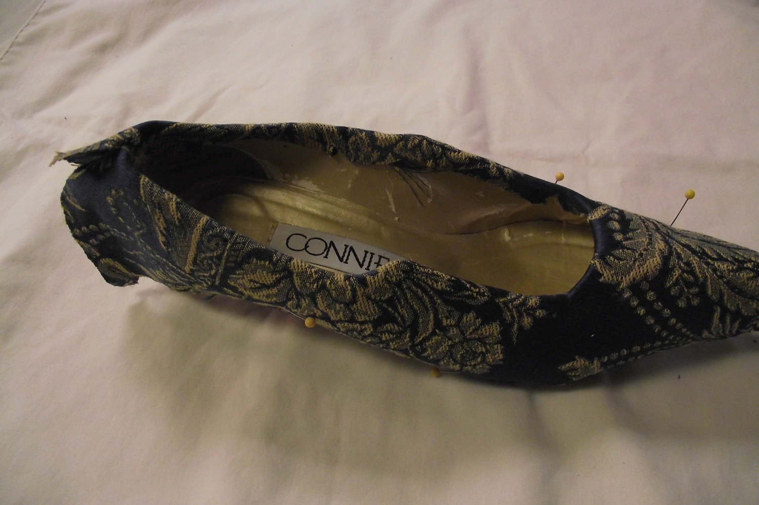Brush glue on inside edge of shoe, pull taught and glue, trim off any eccess fabric. by Kathryn Cover