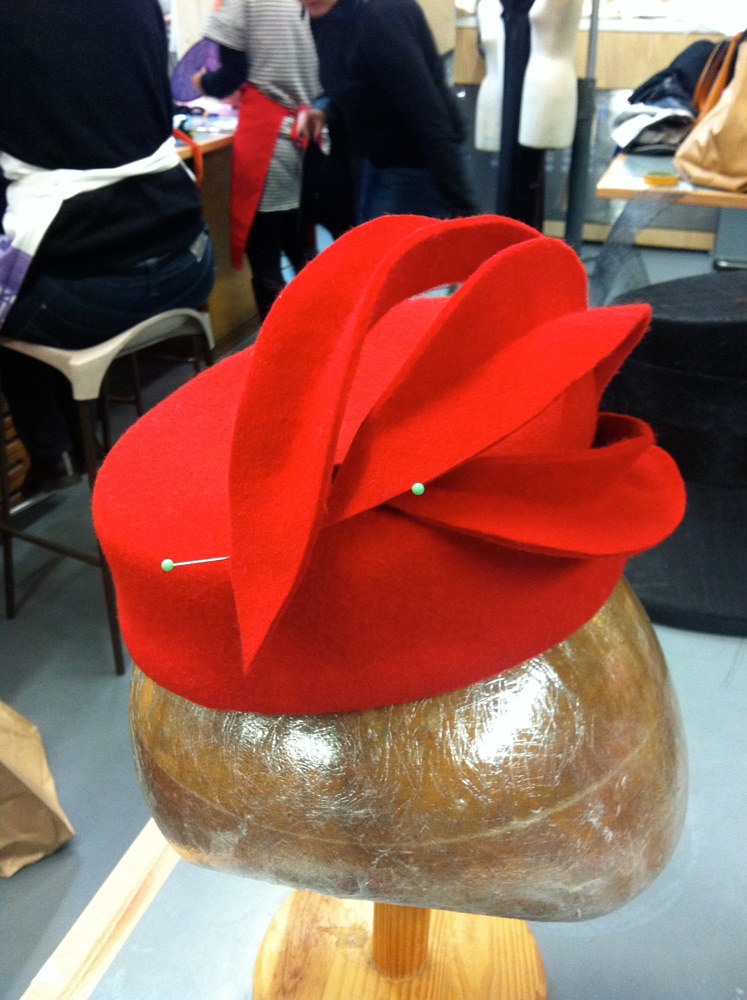 Pinning the 'garnish' on a red cocktail hat by Fiona Menzies