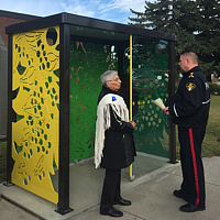 Elder Nora Cummings chatting with a police officer at the opening celebration for the bus shelter.  by Tamara Rusnak