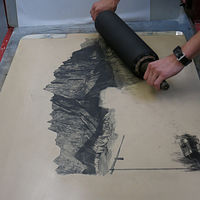 Inking up lithographic stone with roller by Amie Rangel