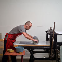 Inking up stone and/or plate on printing press by Amie Rangel