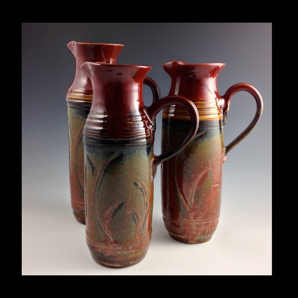 3 RED CARVED TALL PITCHERS by Elaine Clapper